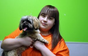 Dogtopia Meadowvale staff poses with a cute morkie